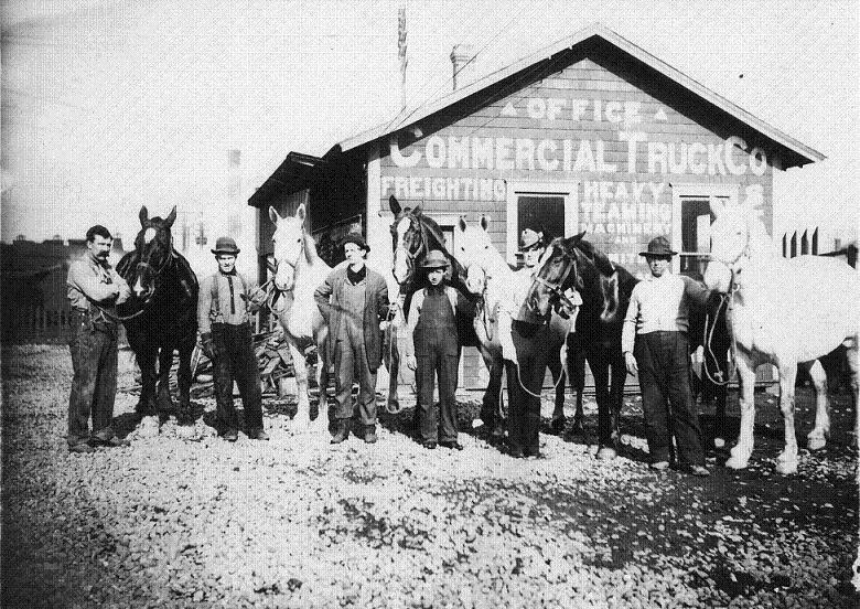 Photo courtesy of Tacoma Public Library. Six unidentified men pose with their horses in front of the offices of the Commercial Truck Co. in the early 1900's.