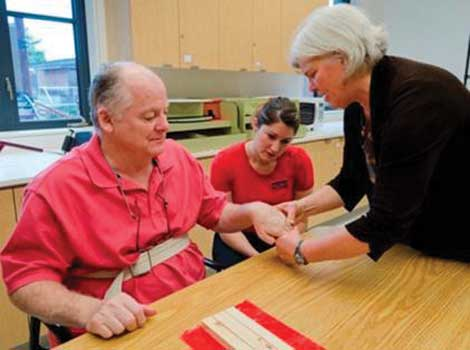 A public patient works with an occupational therapy professor and student in Weyerhaeuser Hall at University of Puget Sound. (Courtesy photo)