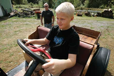 Roy VanBuskirk (background) watches his grandson, Brandon VanBuskirk, at the wheel of a Model A they restored together. (The Dispatch)