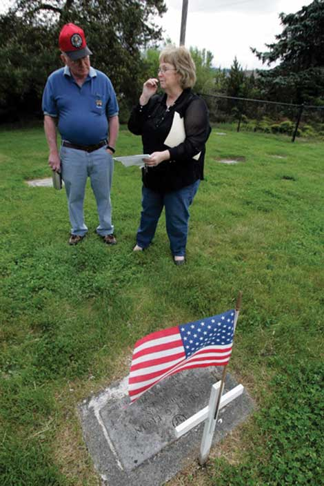 Laurie Porter, manager of Bethany Cemetery, helped connect people in North Dakota with a daughter in Oklahoma of Robert Elgin. Porter is standing at Elgin's gravesite at the cemetery with Doug Korba, a retired Air Force lieutenant colonel who is helping organize a Memorial Day ceremony there. (The Dispatch)