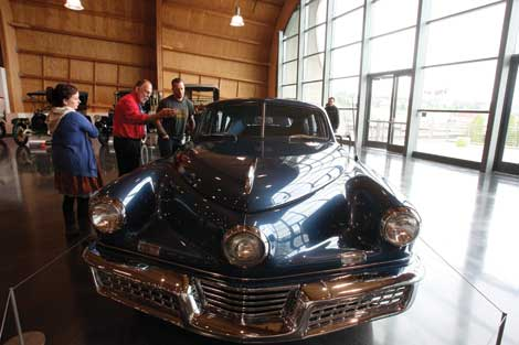 Classic automobiles at LeMay-America's Car Museum include the 1948 Tucker that tour guide Bill Simons (in red shirt)  talks about with admirers. (Jim Bryant/Senior Scene)