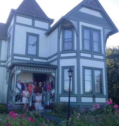 Guests of the Compass Rose bed and breakfast in Coupeville share a moment on the porch with owner Jan Bronson.