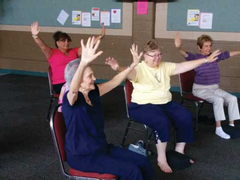 Chair yoga classes like the one taught at University Place Senior Center have enthusiastic participants.