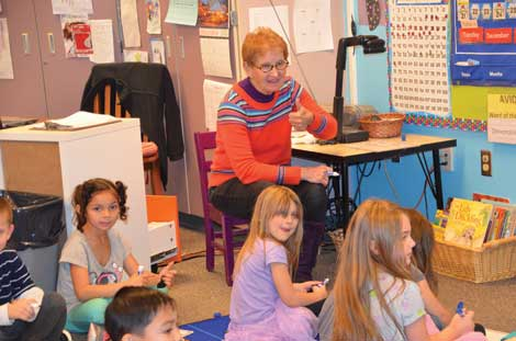 Marcia Madsen gives her kindergarten students at Woodland Elementary School a thumbs-up during a reading and writing assignment. Madsen, a teacher for more than 20 years, is 70 but has no plans for retiring. (Joan Cronk/Senior Scene)