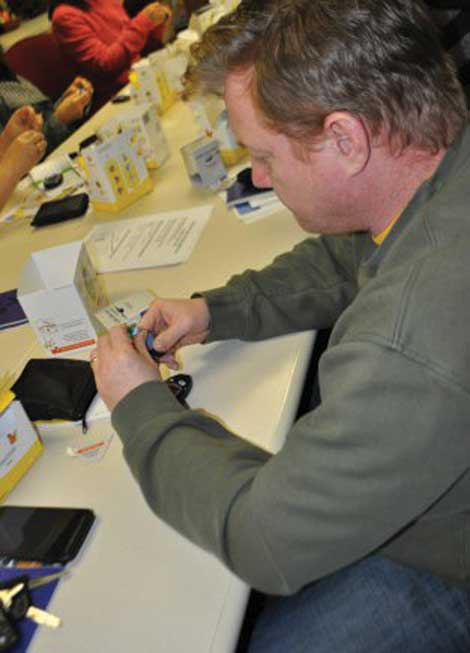 Pat Spaulding learns to test his blood sugar level at the Diabetes Care Center's Essentials Class on Jan. 5 at Madigan Army Medical Center. The class gives an overview of diabetes, treatment and how to test blood sugar levels. (Suzanne Ovel/Army Medicine)