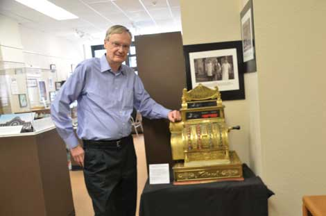 """Bill Baarsma, president of Tacoma Historical Society, shows off a 1909 cash register that was once part of a grocery store that brothers Amil and Solomon Zelinsky ran in Tacoma's Old Town area. """"It still works,"""" said Baarsma. (Joan Cronk/Senior Scene)"""