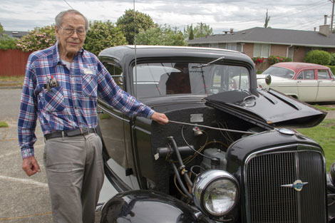 Bob Erickson poses with his 1934 Chevrolet Business Coupe that he bought brand-new for $440 in 1949 when he was 19 years old. In the background is the 1955 Dodge that's one of three vintage automobiles in his stable. (Jim Bryant/for Senior Scene)