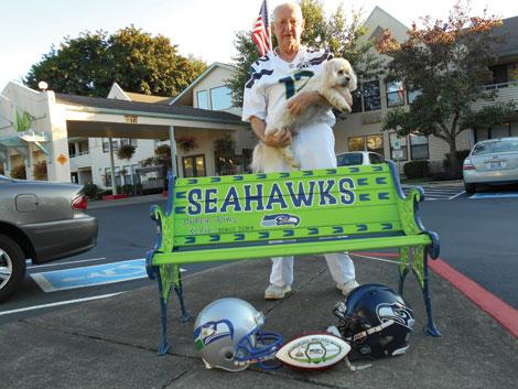 Ed Arnold with the bench he repainted in honor of his favorite football team.