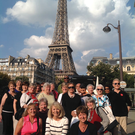 With the Eiffel Tower in the background, a group of American travelers pose for a photo during a visit to Paris.