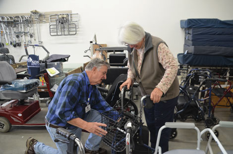 "Gene Schwarz helps customer Pat LaFerriere find the right piece of equipment for a friend who has Parkinson's Disease. ""I don't like to send anything out the door that people don't know how to use,"" said Schwarz. (Joan Cronk/for Senior Scene)"